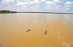 Villagers in canoes ply the wide waters of the Amazon River in Brazil