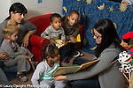 Education Preschool child care 2-3 year olds female teacher reading book to group of boys and girls, another teacher holding listening child