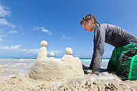Building a sand castle on the white sand beach near Tulum, Mexico