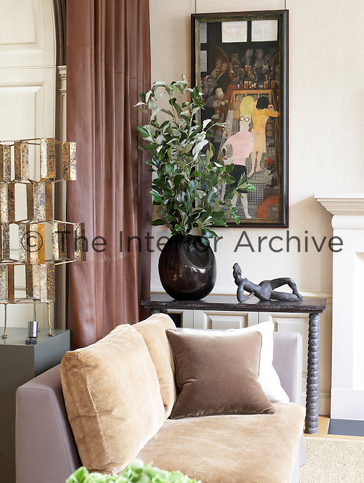 A bronze figurine on a marble side table complements a contemporary painting in the living room
