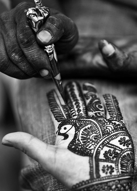 A woman has her hands painted with henna on the street in New Delhi, as on her wedding day, to celebrate  Karwa Chauth. Karwa Chauth is a traditional Hindu and Barelvi festival of married women celebrated in India. Married women fast one whole day without food or water for the long life of their husbands. The ritual signifies extreme love and devotion to the husband, as evidenced by the wife's willingness to suffer for his well being. The women often spend the day preparing in a similar manner to their wedding day - dressing in their finest sari's , hands being painted and waiting for the moon to rise to break their fast with their husbands.