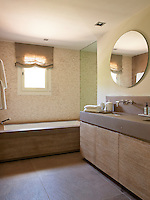 Cool mosaic tiling contrasts with warm limed woodwork used for the bathroom cupboards and bath surround
