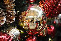 STAFF PHOTO ANDY SHUPE - A line of children is reflected in a Christmas ornament as they wait to see Santa Claus Monday, Dec. 22, 2014, in the Northwest Arkansas Mall in Fayetteville.