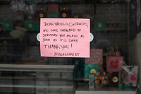 """A sign reads """"Dear Valued Customers / We look forward to serving you again as soon as it is safe / Thank you! / -Management"""" in the window of Woops! Bakery in Newton, Massachusetts, on Sat., March 28, 2020. This bakery, as have many restaurants in the USA, have closed operations during the ongoing Coronavirus (COVID-19) global pandemic."""
