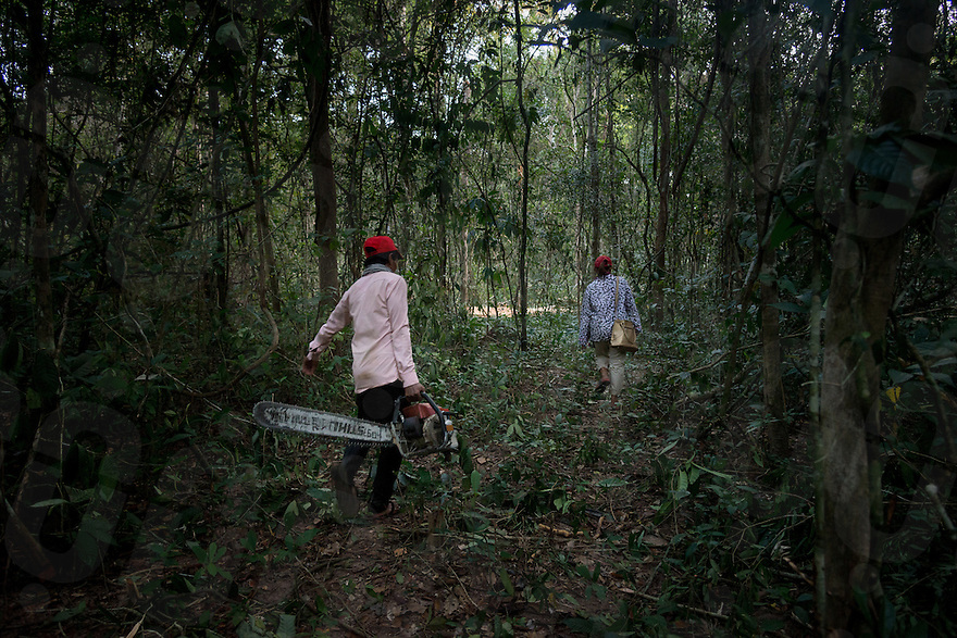 Loun Keuth and Phouk Hong carry a chainsaw to their tractor after confiscating it from illegal loggers. © Antoine Raab / Ruom