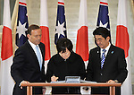 AUSTRALIA, Canberra : Mrs Akie Abe (C) signs the visitors book with Australian Prime Minister Tony Abbott (L) and Japanese Prime Minister Shinzo Abe (R)  at Parliament House in Canberra on July 8, 2014. Defence ties are set to take centre stage when Australia plays host to Japanese Prime Minister Shinzo Abe this week, as the two countries look set to strengthen their relationship through annual leaders' meetings. AFP PHOTO / Mark GRAHAM
