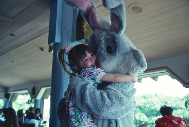 Young girl getting a hug from the Easter Bunny in a restaurant