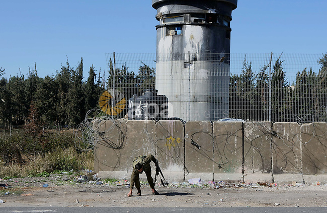 An Israeli soldier inspects the scene where Hammam Masalma hit-and-run left three soldiers injured in al-Arroub refugee camp, near the West Bank city of Hebron, November 6, 2014. The hit-and-run incident on the main Bethlehem-Hebron road on Wednesday night was the third such vehicular attack on Israeli soldiers and civilians in recent weeks, although the previous two took place in Jerusalem. Photo by Mamoun Wazwaz