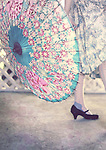 The legs of a young woman wearing vintage clothes walking away twirling a vintage summer parasol