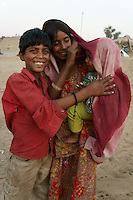 brother and sister care about  a baby in dsert area next  camel fair in holy city Pushkar while sunset time