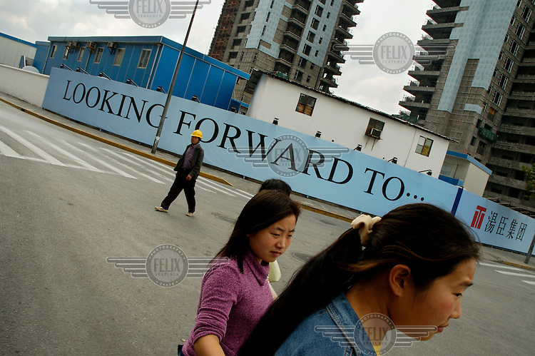 People in the Pudong financial district, next to a sign outside a construction site reading 'Looking forward to ...'. In a country of rising inequality, some people have more to look forward to than others.