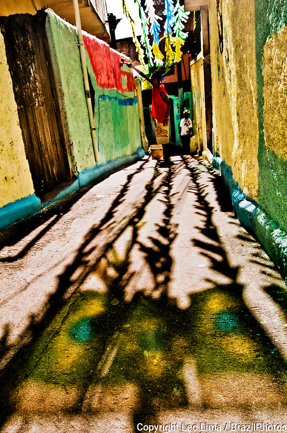 2010 World Cup street decoration in Favela do Jacarezinho, Rio de Janeiro, Brazil.  Man painting alley walls with Brazil colors. Reflection of Brazil flag on floor in foreground. Since January 2013 Favela do Jacarezinho has a Pacifying Police Unit ( Unidade de Polícia Pacificadora, also translated as Police Pacification Unit ), abbreviated UPP, a law enforcement and social services program which aims at reclaiming territories, more commonly favelas, controlled by gangs of drug dealers.