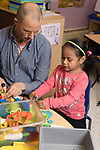 Education Preschool 3 year olds male intern working with girl using toy figures, talking, playing