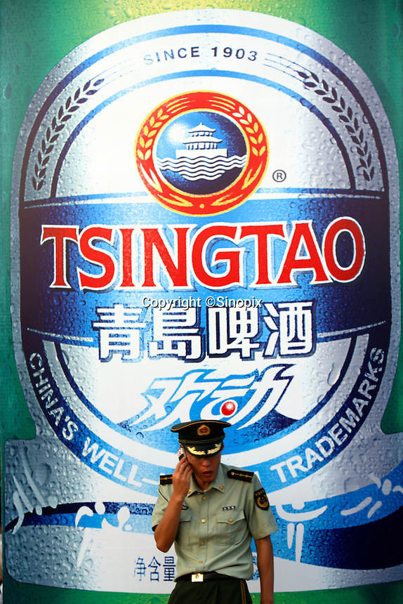 A Chinese army soldier stands next to a large Tsingtao Beer advert during the Qingdao Beer Festival in Qingdao, China. Tsingtao Brewery is China's largest brewery, founded in 1903 by German settlers, it claims about 12% of domestic market share..