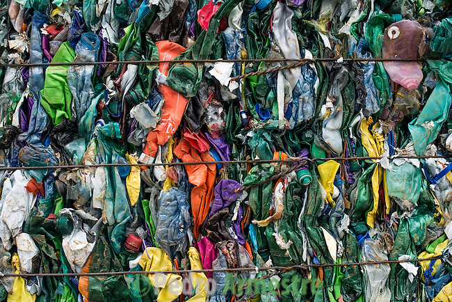 "A picture taken on November 3, 2015 shows stacks of plastic waste collected in the sea by fishermen at a plastic processing plant in Chiva, near Valencia. Ecoalf, a Spanish Madrid-based firm founded in 2010, has already launched ""a new generation"" of clothes and accessories made from plastic bottles, old fishing nets and used tires found on land.  © Pedro ARMESTRE"