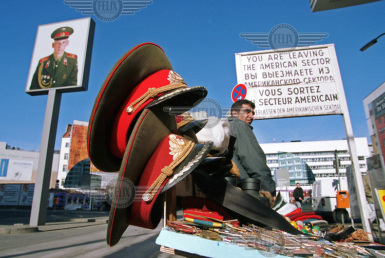 Stall selling military visor hats and souvenirs at the Checkpoint Charlie in the Berlin-Mitte area of the city.  The checkpoint was formerly one of three crosssing points between East and West Germany on the Berlin wall during the Cold War.