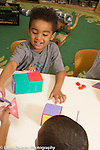 Education Preschool 3-4 year olds two boys comparing shapes as they build with magnet blocks