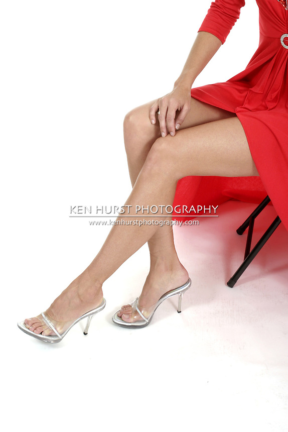 View of the beautiful legs of a woman in a long red dress sitting on a stool.