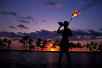 Silhouette of a man holding a torch, blowing a conch shell and standing ankle deep in the water at  Anaehoomalu Bay in Waikoloa. Background shows a row of silhouetted palm trees and a fiery sunset.