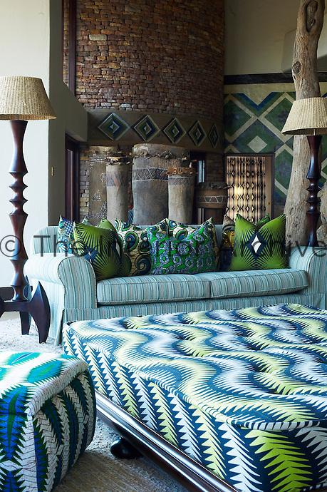 A communal seating area at Singita Pamushana Lodge, Malilongwe Trust, Zimbabwe with a sofa and ottoman in patterned upholstery