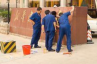 Daytime landscape view of four men working on the signage in front of a commercial building in the Guǎnchéng Huízú Qū of Zhengzhou in Henan province.  © LAN