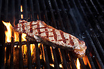 Sizzling Steak on Grill  ready to be served, kissed by flames, with classic gridiron pattern.  Yum.