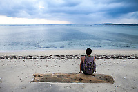A man sits on the beach on the tiny island of Gili Air, Indonesia.
