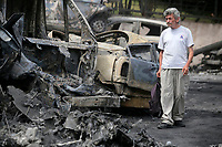 Pictured: A man walks next to burned cars in the aftermath of the forest fire which has claimed dozens of lives in the Mati area of Rafina, Greece. Tuesday 24 July 2018<br /> Re: Deaths caused by wild forest fires throughout Greece.