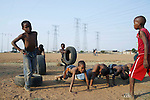 SOWETO, SOUTH AFRICA - SEPTEMBER 14: Unidentified boys warm up before a soccer a practice on September 14, 2007 in the Diepkloof section Soweto, South Africa. Soccer is the most popular sport in South Africa, and a because of the upcoming World Cup 2010 in South Africa the interest is increasing. For the first time the World Cup will be held on the African continent. South Africa doesn't have an organized youth soccer program and many teams and players struggle with lack of funds, to buy equipment and money for transport to games. .(Photo by Per-Anders Pettersson)....