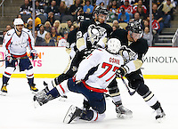 Nick Bonino #13 and Brian Dumoulin #8 of the Pittsburgh Penguins hit T.J. Oshie #77 of the Washington Capitals in the first period during the game at Consol Energy Center in Pittsburgh, Pennsylvania on December 14, 2015. (Photo by Jared Wickerham / DKPS)
