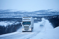Viking Transport Service truck travels through arctic wilderness at nightfall by Kilpisjarvi on route from Norway into Finland