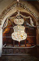 An archway and religious heraldry made of human bones and used as decoration in the Chapel of All Saints Cemetery. The bone motifs were created from skeletons that had accumulated since the 14th century. Kutna Hora, Bohemia, Czech Republic.