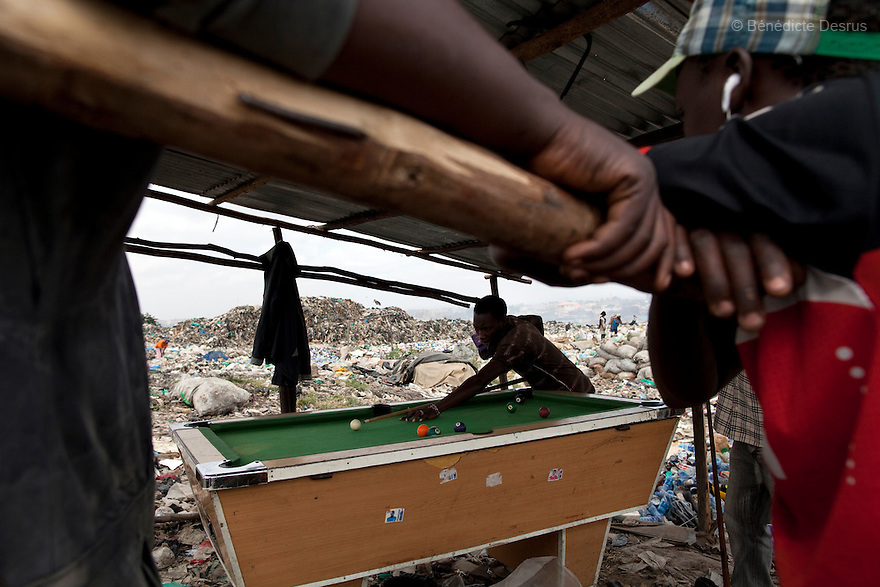 13 february 2013 - Dandora dumpsite, Nairobi, Kenya - Men play pool during breaks between work at the Dandora dumpsite, one of the largest and most toxic in Africa. Located near slums in the east of the Kenyan capital Nairobi, the open dump site was created in 1975 and covers 30 acres. The site receives 2,000 tonnes of unfiltered garbage daily, including hazardous chemical and hospital wastes. It is a source of survival for many people living in the surrounding slums, however it also harms children and adults' health in the area and pollutes the Kenyan capital. Photo credit: Benedicte Desrus