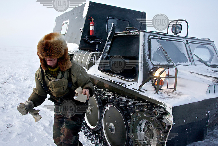 Andrei exits his snow tank to deliver light bulbs to colleagues at an isolated camp set up by oil and gas prospecting company Siesmorevzedka deep in the Arctic tundra. /Felix Features