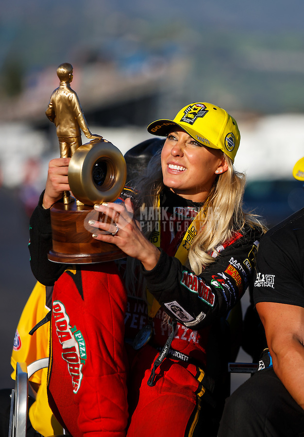 Feb 12, 2017; Pomona, CA, USA; NHRA top fuel driver Leah Pritchett reacts as she looks at her her trophy as she celebrates after winning the Winternationals at Auto Club Raceway at Pomona. Mandatory Credit: Mark J. Rebilas-USA TODAY Sports
