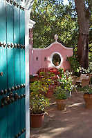 A turquoise painted studded door opens onto a courtyard with a comfortable sitting area