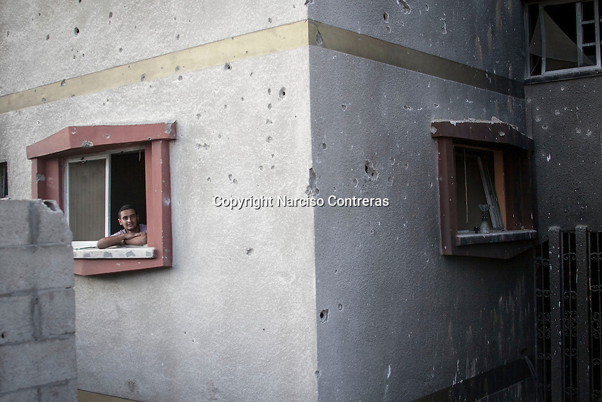 """In this Friday, Aug. 15, 2014 photo, a piece of artillery shell and one Palestinian man are seen at the windows ledges of a house building in Shuyaja neighborhood after the """"Protective Edge"""" Israeli military operation reached a cease-fire in Gaza. After a five days truce was declared on 13th August between Hamas and Israel, civilian population went back to what remains from their houses and goods in Gaza Strip. (Photo/Narciso Contreras)"""