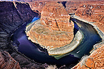 A boat sails along the Colorado River as it winds through Horseshoe Bend in Arizona
