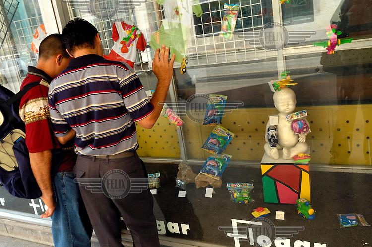 Two men examine a small toyshop window display in downtown Havana.