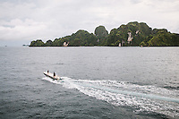 A speedboat cross the water for a dive spot around Farondi, Misool, Raja Ampat, West Papua, Indonesia