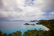 Overlooking a beautiful, hidden Caribbean cove filled with vacationers and tourists relaxing on the beach