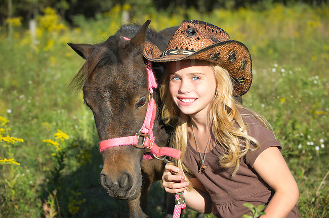 Young blonde cowgirl holding her miniature horse, smiling thirteen year old girl with pretty blue eyes.
