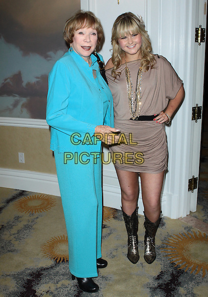 SHIRLEY MacLAINE & ASHLEE KEATING.Big Brothers Big Sisters Spring Luncheon 2010  held at The Beverly Hills Hotel, Beverly Hills, California, USA..April 27th, 2010.full length dress hand on hip boots cowboy ruched beige necklaces gold flower in hair blue turquoise trousers jacket side suit .CAP/ADM/TC.©T. Conrad/AdMedia/Capital Pictures.