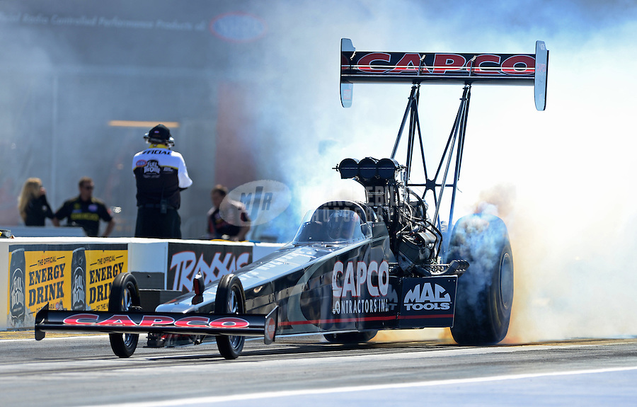 Apr. 13, 2012; Concord, NC, USA: NHRA top fuel dragster driver Steve Torrence does a burnout during qualifying for the Four Wide Nationals at zMax Dragway. Mandatory Credit: Mark J. Rebilas-