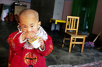 CHINA. Beijing. A young orphan in an orphanage outside of Beijing. There are currently millions of orphans in China living in orphanages spread throughout the country. As a result of China's one-child policy, many children are abandoned or given up if they suffer from any physical or mental handicap as the parents strive to have a child born 'normal' and well. This has led to may children being abandoned to live in state and privately-owned orphanages.