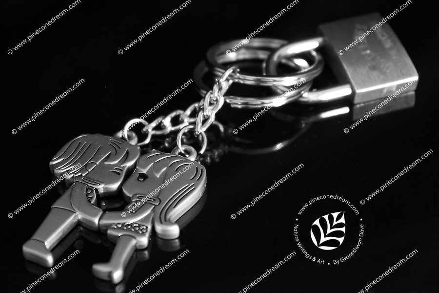 """Black & white stock image of metal boy-girl pair key-chain locked together. <br /> <br /> To view the same image in color visit the gallery-""""Food & Other Still Life""""."""