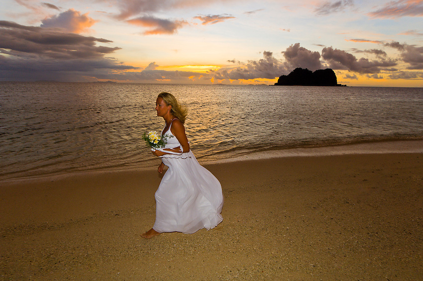 A pregnant bride after wedding ceremony, Vomo Lailai at sunset in background, Vomo Island, Fiji Islands
