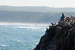 Fishermen fishing on the cliffs of Bordeira in the Algarve region of Portugal.