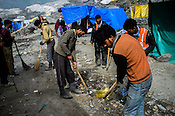 Workers clean up the garbage left behind by the pilgrims on the base of the Holy Cave along the Amarnath trekking route in Kashmir, India. Hindu pilgrims brave sub zero temperature and high latitude passes and make their pilgrimage to reach the sacred Amarnath cave, which houses a lingam - a stylized phallus, worshiped by Hindus as a symbol of God Shiva. Photo: Sanjit Das/Panos