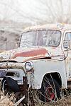 An old, rusty truck sits in a field in rural America.